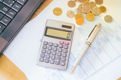 Calculatrice et stylo sur un papier avec le graphique DOF peu profond Photographie stock