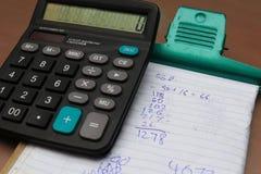 Calculatrice et un livre Photos libres de droits