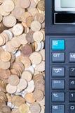Calculatrice et une pile de pièces de monnaie Images libres de droits