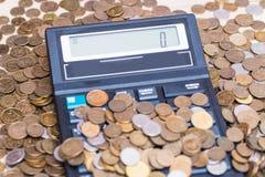 Calculatrice et une pile de pièces de monnaie Photos stock
