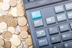 Calculatrice et une pile de pièces de monnaie Photo stock