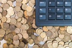 Calculatrice et une pile de pièces de monnaie Images stock