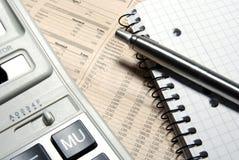 Calculatrice financière, crayon lecteur en acier et cahier. Image stock