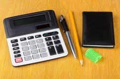 Calculatrice électronique, bloc-notes, stylo, affûteuse et crayon Images stock