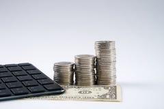 Calculatrice moderne noire avec des billets de banque et des pièces de monnaie d'isolement sur le blanc Image libre de droits