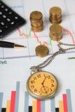 Calculatrice, montre et piles de pièces de monnaie Images stock