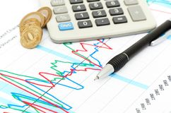 Calculatrice, pièces de monnaie et crayon lecteur s'étendant sur le diagramme. Photographie stock