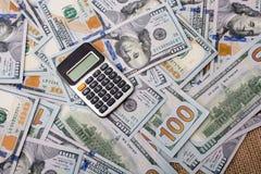 Calculatrice placée au-dessus des billets de banque de dollar US Images libres de droits