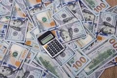 Calculatrice placée au-dessus des billets de banque de dollar US Images stock
