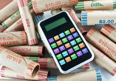 Calculatrice se reposant sur des emballages de pièce de monnaie Photos stock