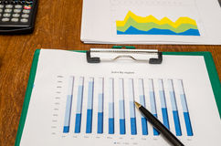 Calculatrice, stylo et diagrammes financiers Photos stock