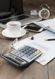 Calculatrice sur la table de travail avec le téléphone portable de carnet d'ordinateur et Image stock