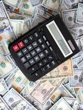 Calculatrice sur le fond de cent billets d'un dollar Images stock