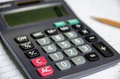 Calculatrice sur les écritures blanches Photographie stock libre de droits