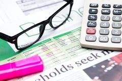 Calculatrice, verres et marqueur de stylo sur le fond de journal Photo libre de droits