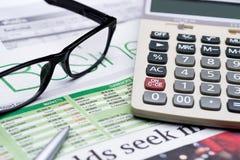 Calculatrice, verres et stylo sur le fond de journal Image stock