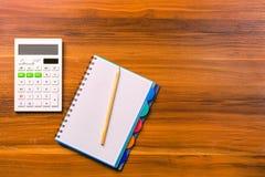 Calcule, notebooke e lápis na tabela de madeira fotografia de stock