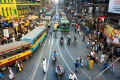 CALCUTTA, LA INDIA: Los peatones cruzan el camino delante de las motocicletas, de los coches y de los autobuses en los cruces Foto de archivo libre de regalías