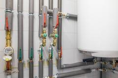 caldaia bianca per il riscaldamento dell'acqua e rete di tubazioni con il tubo grigio Immagine Stock Libera da Diritti