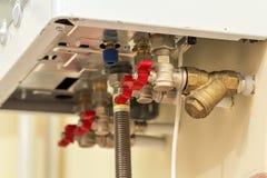Caldaia dello scaldabagno a gas per riscaldamento domestico, vista dal basso Concetto dell'installazione, del collegamento e di m fotografie stock