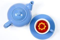 Caldaia e tazza blu di tè con i fiori Immagini Stock