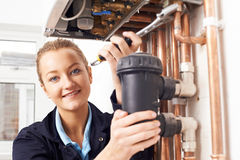 Caldaia femminile del riscaldamento di Working On Central dell'idraulico Fotografie Stock Libere da Diritti