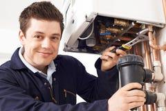 Caldaia maschio del riscaldamento di Working On Central dell'idraulico Immagine Stock