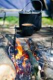 Caldeira do turista com alimento e uma caneca com água em um fogo imagens de stock royalty free