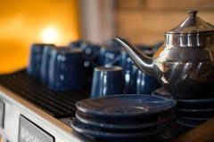 Caldera con las tazas y los platillos en cafetería Imagenes de archivo