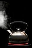 Caldera de té con el agua hirvienda en fondo negro Foto de archivo