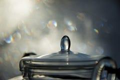 Caldera de té de cristal con el fondo del bokeh imágenes de archivo libres de regalías