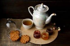 Caldera de té de la porcelana y taza de té con té verde Rosas presionadas en una tabla de madera Tres pequeños tarros de la baya  Foto de archivo
