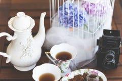 Caldera de té, tazas de té y cámara Fotografía de archivo