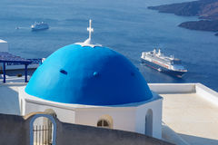 Caldera with dome against ships on Santorini island in Greece Stock Photography