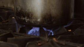 Caldera en una estufa con las llamas azules en la cámara lenta metrajes