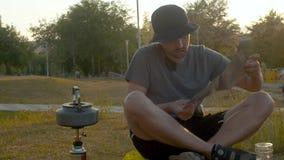 Caldera en una estufa de campo Un hombre ajusta el gas almacen de metraje de vídeo