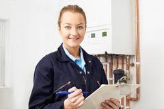 Caldera femenina de la calefacción de Working On Central del fontanero imagen de archivo