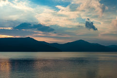Caldera lake on dusk with mountain silhouettes on the background. Caldera lake on dusk mist with mountain silhouettes in fog on the background. Lake Ashi, Hakone Stock Photography