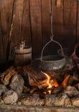 Caldera que cocina sobre un fuego abierto en la cabina fotografía de archivo