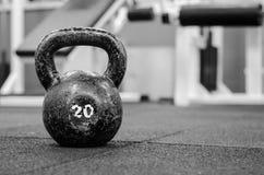 Caldera vieja y oxidada Bell en el piso del gimnasio en blanco y negro Foto de archivo
