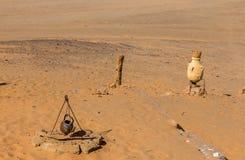 Caldera y jarro en un fondo de la arena Fotografía de archivo