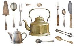 Calderas del metal del vintage, cucharas, bifurcaciones, cuchillo, pinzas del azúcar, y pala antiguos de la torta aislada en un f imagen de archivo libre de regalías