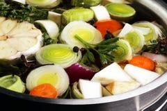 Caldo com cenouras, vários legumes frescos das cebolas em um potenciômetro - c Imagem de Stock Royalty Free