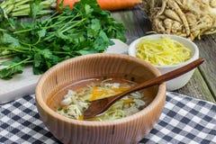 Caldo de galinha com cenouras, aipo, salsa e macarronete em de madeira Imagens de Stock Royalty Free