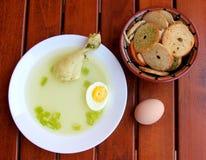 Caldo de pollo con el huevo, la pierna de pollo y las migas de pan secas Foto de archivo libre de regalías