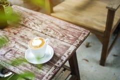 Caldo di cappuccino sulla tavola di legno con la priorità alta vaga dell'albero delle foglie Immagine Stock Libera da Diritti