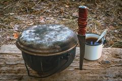 A caldron, a knife and a mug on a wooden stand in outdoor. Hiking set.  stock images