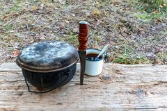 A caldron, a knife and a mug on a wooden stand in outdoor. Tourist. A caldron, a knife and a mug on a wooden stand in outdoor. Tourist stock photos