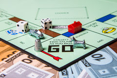 Pieces of a monopoly game. CALDWELL, IDAHO/USA - MARCH 16, 2015: Game pieces from game Monopoly sitting near the start Royalty Free Stock Photos