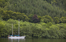 Caledonian canal with sailboat and forest in Scotland Stock Photography